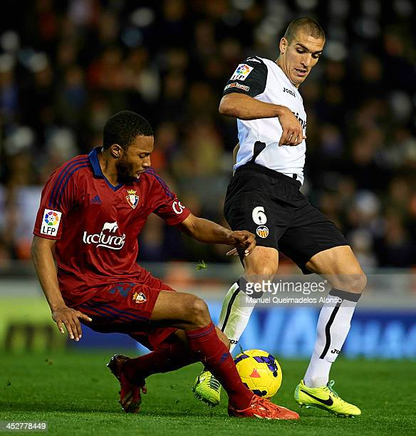 Oriol Romeu of Valencia competes for the ball with Jordan Loties of Osasuna during the La Liga match between Valencia CF and CA Osasuna at Estadio...