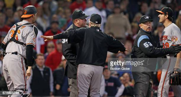 Orioles starting pitcher Kevin Gausman right and catcher Caleb Joseph left argue with home plate umpire Sam Holbrook who had just ejected Gausman...