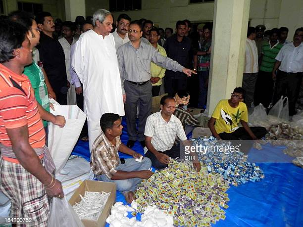 Orissa state chief minister Naveen Patnaik watches as relief items are packaged for distribution to cyclone evacuees in the eastern city Bhubaneswar...