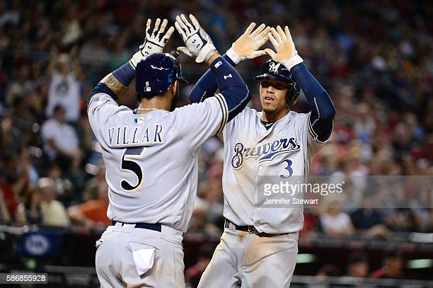 Orlando Arcia and Jonathan Villar of the Milwaukee Brewers celebrate after teammate Ryan Braun hits a three run home run during the sixth inning at...