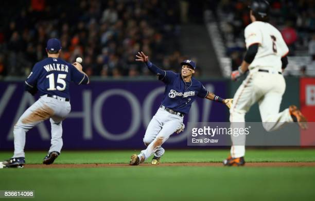 Orlando Arcia flips the ball to Neil Walker of the Milwaukee Brewers who dropped the ball to allow Jarrett Parker of the San Francisco Giants to be...