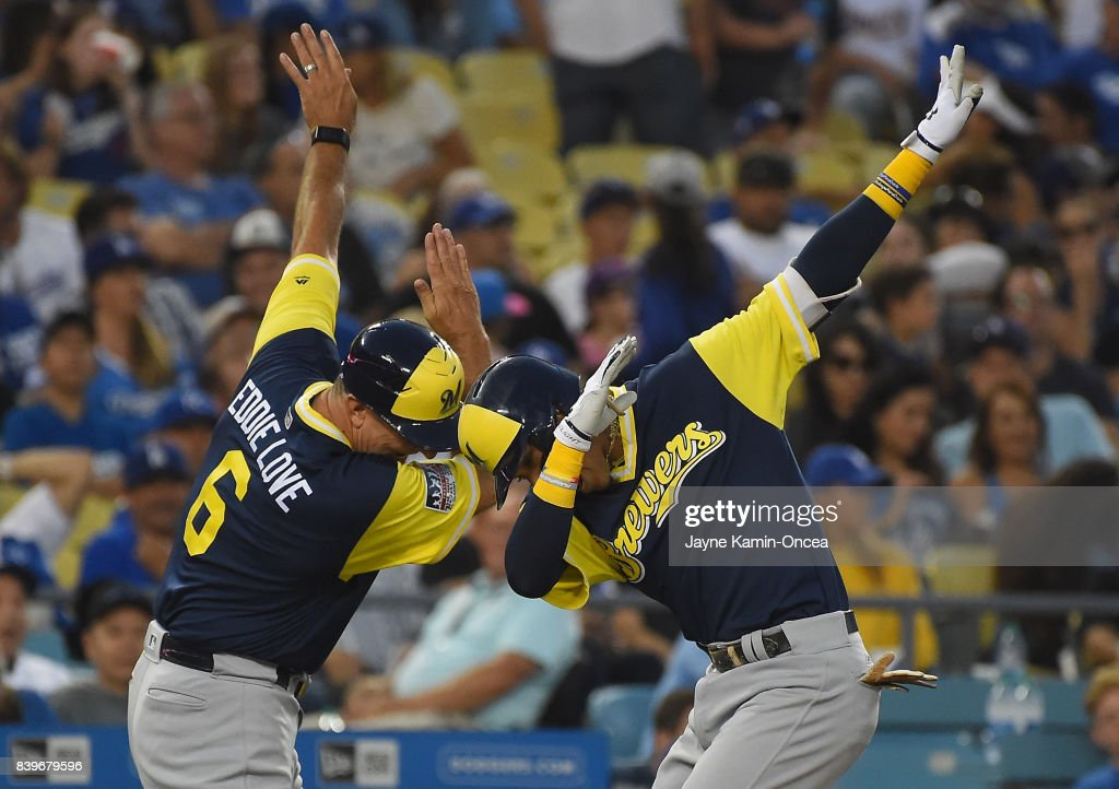 Orlando Arcia #3 of the Milwaukee Brewers celebrates a two run home run with third base coach Ed Sedar #6 of the Milwaukee Brewers in the fifth inning of the game against the Los Angeles Dodgers at Dodger Stadium on August 26, 2017 in Los Angeles, California.
