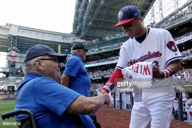 Orlando Arcia of the Milwaukee Brewers presents Korean War veteran Don Wiegand with a uniform before the game against the Baltimore Orioles at Miller...