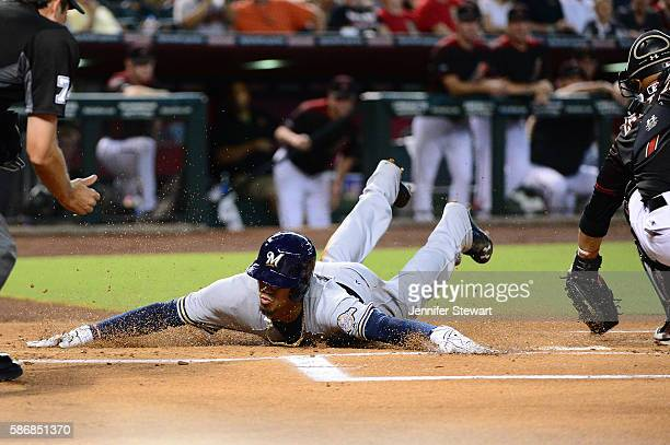 Orlando Arcia of the Milwaukee Brewers safely slides into home plate behind Welington Castillo of the Arizona Diamondbacks during the first inning at...