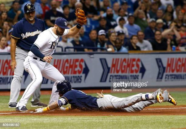 Orlando Arcia of the Milwaukee Brewers slides safely into third base ahead of third baseman Evan Longoria of the Tampa Bay Rays after hitting a...