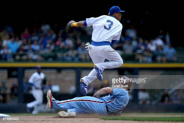 Orlando Arcia of the Milwaukee Brewers turns a double play past Andrew Knapp of the Philadelphia Phillies in the seventh inning at Miller Park on...