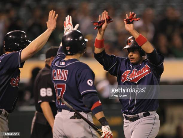 Orlando Cabrera is congratulated by Jack Hannahan and ShinSoo Choo of the Cleveland Indians after he scored on in the ninth inning to give the...