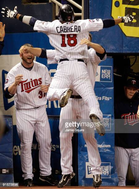 Orlando Cabrera of the Minnesota Twins is congratulated by teammates after hitting a home run against starting pitcher Rick Porcello of the Detroit...
