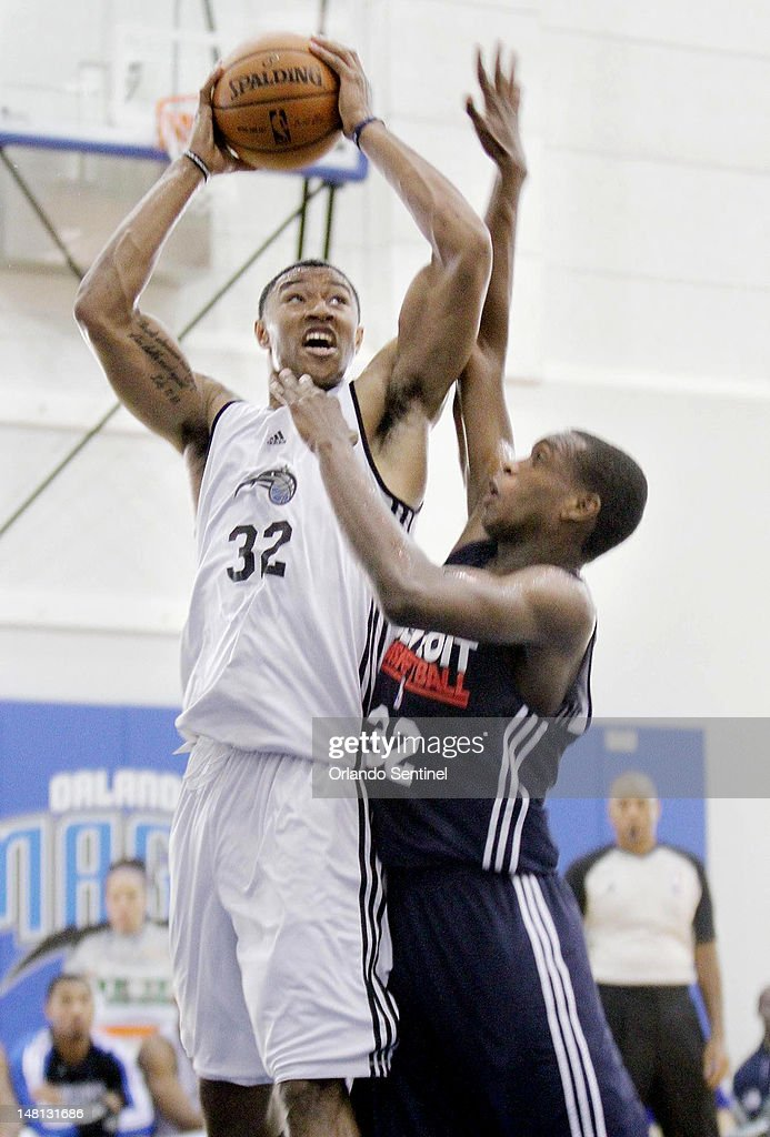 Orlando forward Justin Harper (32, white jersey) looks to pass over Detroit guard Khris Middleton (32, dark jersey) during the Detroit Pistons at Orlando Magic summer league game at the Amway Center on Tuesday, July 10, 2012.
