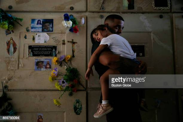 Orlando Gonzalez holds his daughter Nahielys as they attend the funeral of their neighbor Victor Ruiz Ramos in Corozal Puerto Rico on Oct 02 2017...