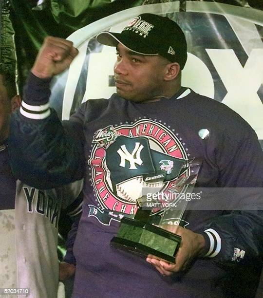 Orlando Hernandez of the New York Yankees holds the Most Valuable Player Trophy in their locker room after his team's 61 victory over the Boston Red...
