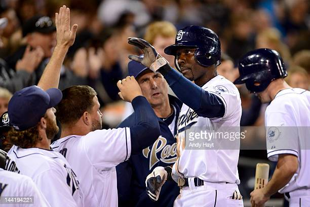 Orlando Hudson is congratulated by teammates of the San Diego Padres on the dugout steps after scoring a run against the Miami Marlins at Petco Park...
