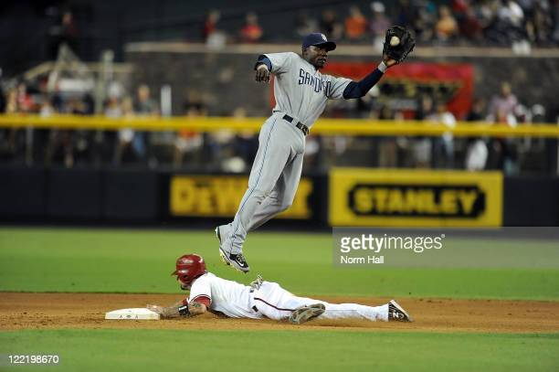 Orlando Hudson of the San Diego Padres catches a throw from the catcher as he jumps over a sliding Ryan Roberts ##14 of the Arizona Diamondbacks at...