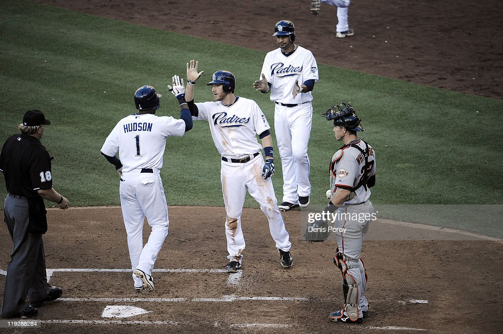 <a gi-track='captionPersonalityLinkClicked' href=/galleries/search?phrase=Orlando+Hudson&family=editorial&specificpeople=203242 ng-click='$event.stopPropagation()'>Orlando Hudson</a> #1 of the San Diego Padres is congratulated by <a gi-track='captionPersonalityLinkClicked' href=/galleries/search?phrase=Chris+Denorfia&family=editorial&specificpeople=702417 ng-click='$event.stopPropagation()'>Chris Denorfia</a> #13 as Eli Whiteside #22 of the San Francisco Giants looks on after Hudson hit a three-run homer during the third inning of a baseball game Petco Park on July 16, 2011 in San Diego, California.