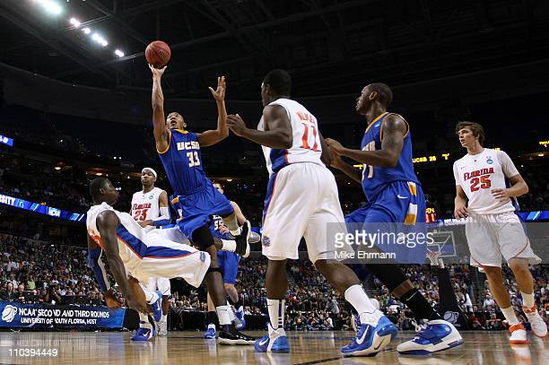 Orlando Johnson of the UC Santa Barbara Gauchos drives for a shot attempt against Vernon Macklin of the Florida Gators during the second round of the...
