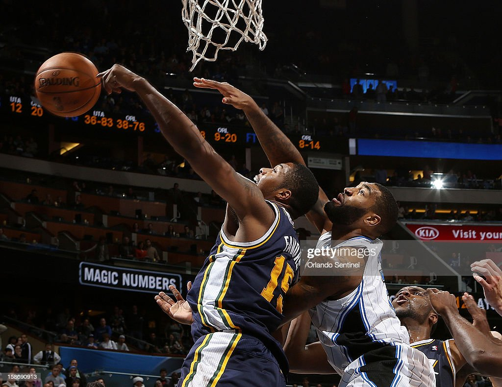 Orlando Magic center Kyle O'Quinn and Derrick Favors from the Utah Jazz fight for a rebound on Sunday, December 23, 2012, at the Amway Center in Orlando, Florida. The Utah Jazz defeated the Orlando Magic, 97-93.