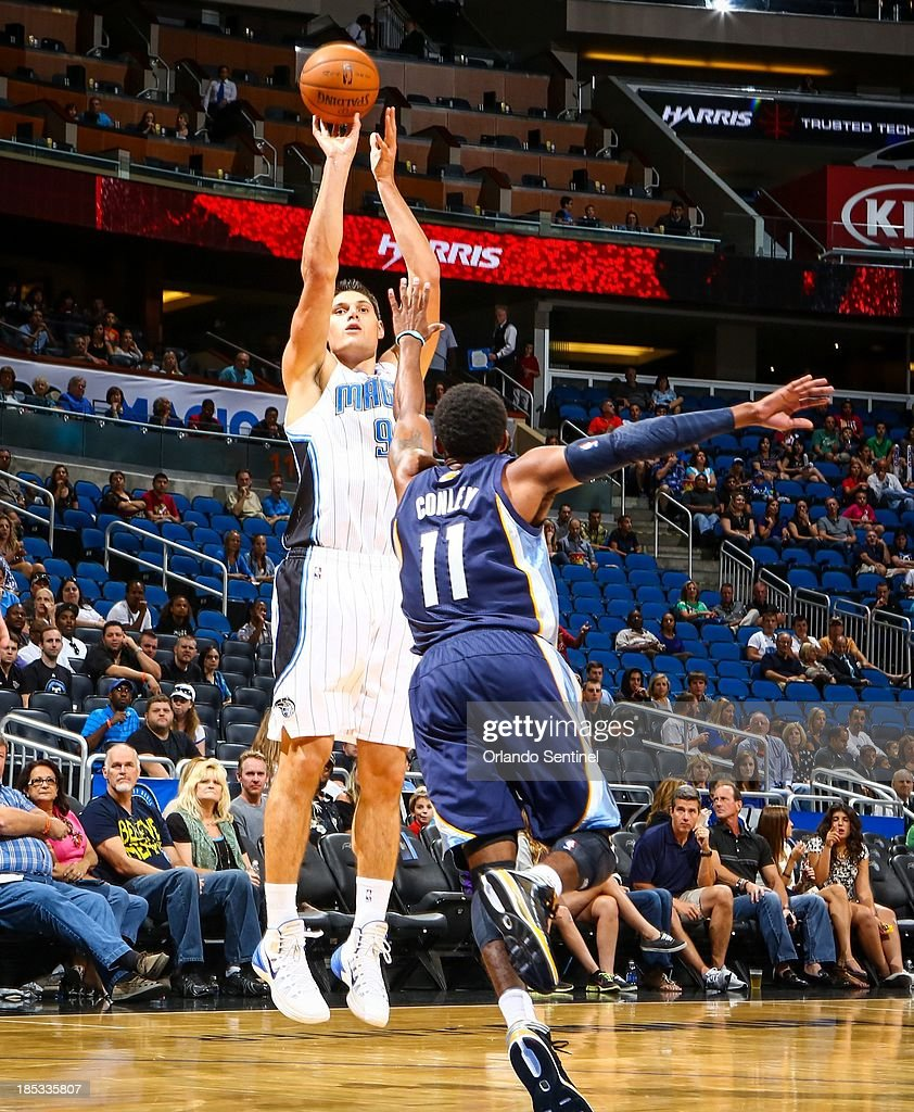 Orlando Magic center Nikola Vucevic (9) shoots over the Memphis Grizzlies' Mike Conley (11) during first-half action of a preseason game at the Amway Center in Orlando, Florida, on Friday, October 18, 2013.