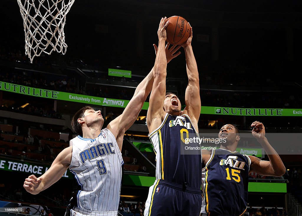Orlando Magic center Nikola Vucevic tries to snag a rebound away from Enes Kanter, center, and Derrick Favors, right, during an NBA game on Sunday, December 23, 2012, at the Amway Center in Orlando, Florida. The Utah Jazz defeated the Orlando Magic, 97-93.