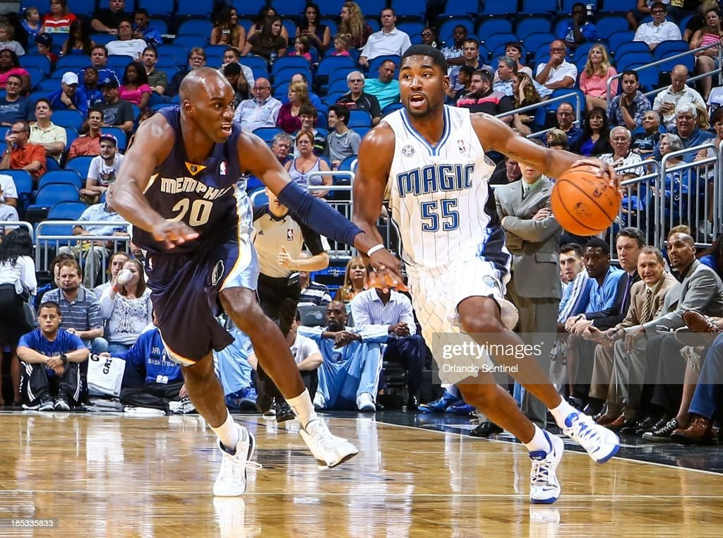 Orlando Magic guard E'Twaun Moore (55) drives past the Memphis Grizzlies' Quincy Pondexter (20) during the first half of a preseason game at the Amway Center in Orlando, Florida, on Friday, October 18, 2013.