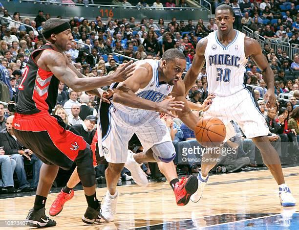 Orlando Magic guard Gilbert Arenas dribbles through Toronto Raptors forward Ed Davis during the first half at Amway Arena in Orlando Florida Friday...