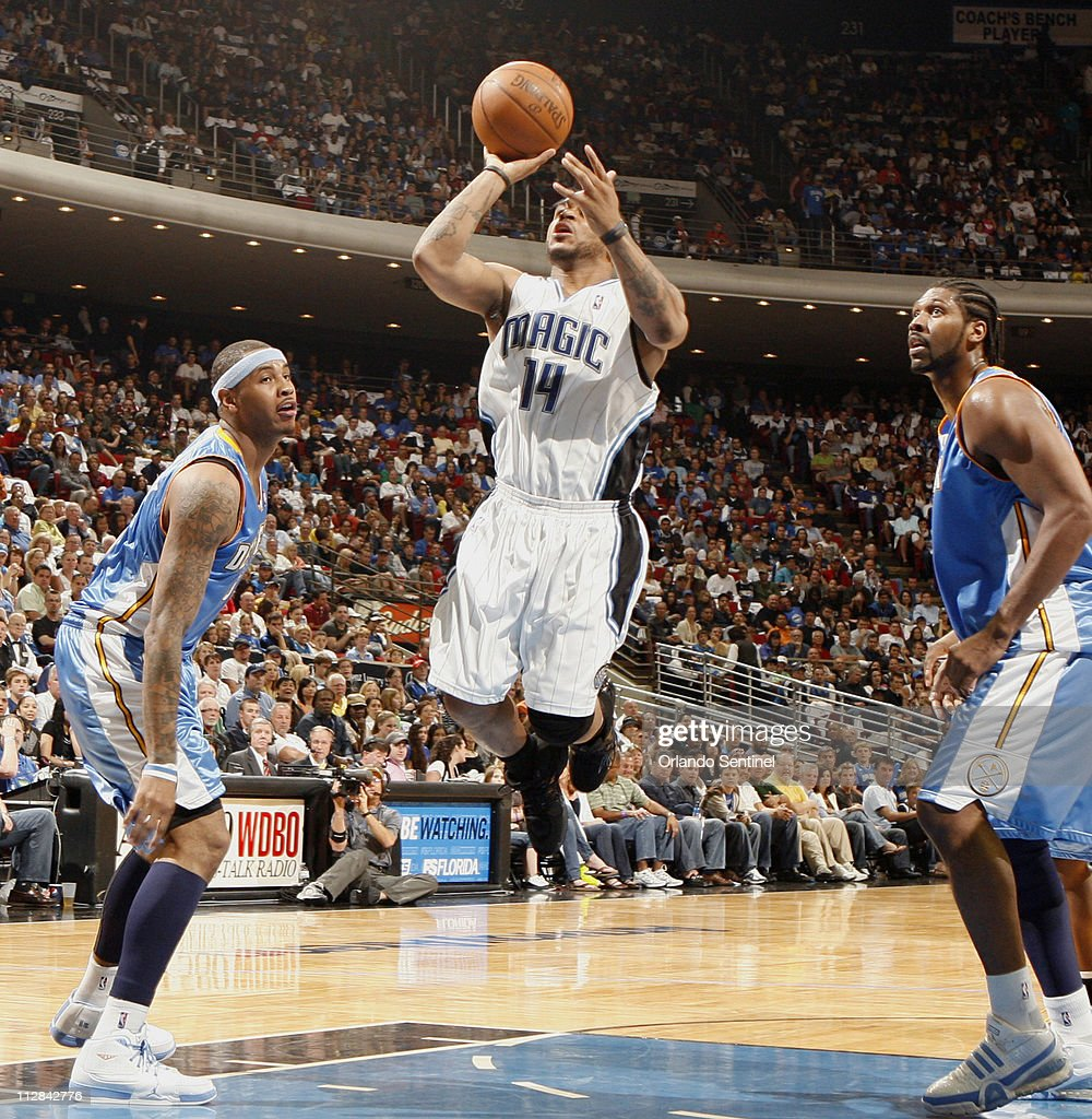 Orlando Magic guard Jameer Nelson (14) sails between Denver Nuggets' Carmelo Anthony (15) and Nene (31) during an NBA game at Amway Arena in Orlando, Florida, Sunday, March 28, 2010. Orlando won 103-97.