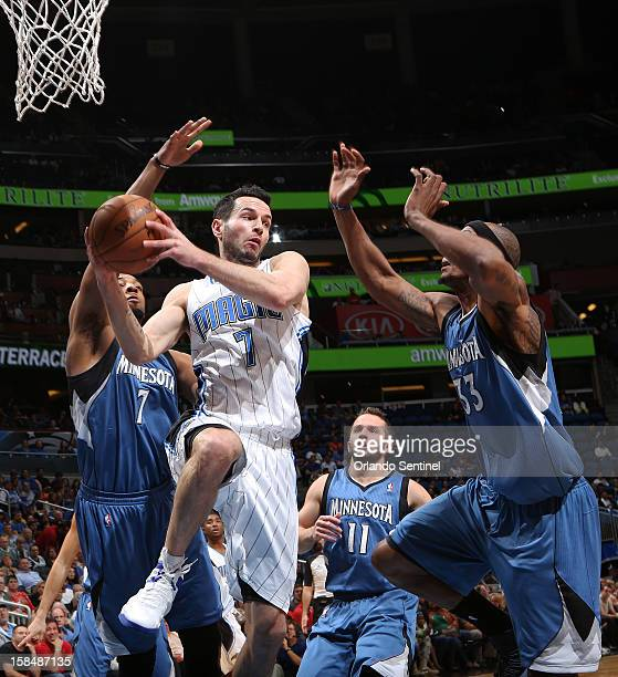 Orlando Magic guard JJ Redick looks to pass as he drives between Derrick Williams left and Dante Cunningham right of the Minnesota Timberwolves...