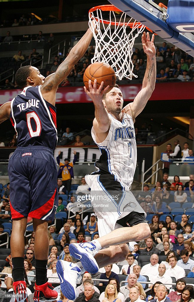 Orlando Magic guard J.J. Redicka (7) scores under Atlanta Hawks guard Jeff Teague (0) during an NBA game at the Amway Center on Wednesday, December 12, 2012.