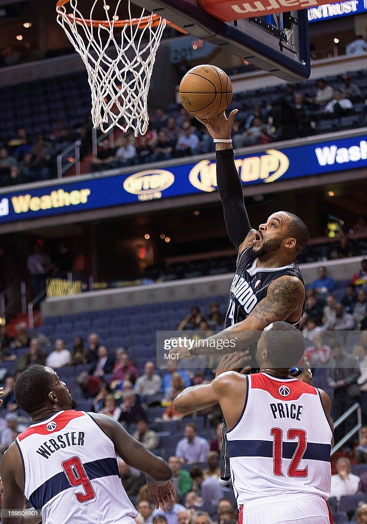 Orlando Magic point guard Jameer Nelson (14) shoots over Washington Wizards small forward Martell Webster (9), left and point guard A.J. Price (12) during the first half of their game played at the Verizon Center in Washington, D.C., Monday, January 14, 2013.