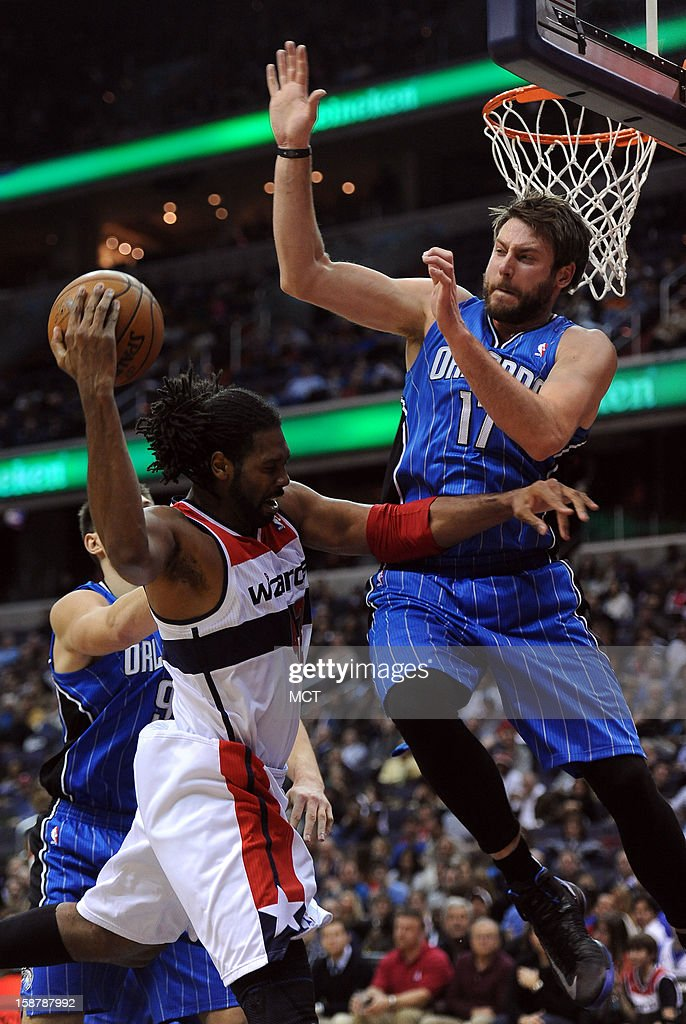 Orlando Magic power forward Josh McRoberts (17) commits a technical foul with a hard foul against Washington Wizards center Nene (42), left, in the fourth quarter at the Verizon Center in Washington, D.C., Friday, December 28, 2012. The Wizards defeated the Magic, 105-97.