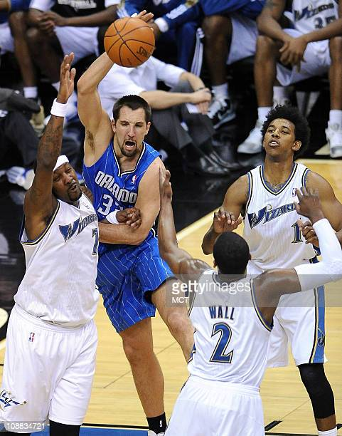 Orlando Magic power forward Ryan Anderson attempts to knock and offensive rebound to a teammate while surround by Washington Wizards power forward...