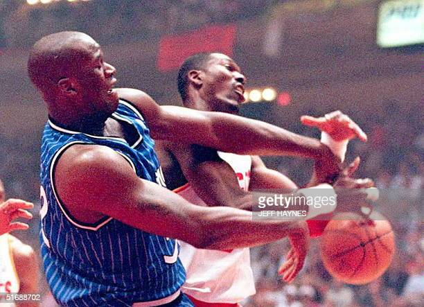 Orlando Magic Shaquille O'Neal battles for control of the ball with Houston Rockets Hakeem Olajuwon 11 June during the first quarter of game three of...