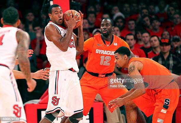 Orlando Sanchez of the St John's Red Storm holds the ball against Baye Moussa Keita and Michael Gbinije of the Syracuse Orange during the game at...