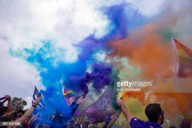 Orlando supporters release rainbow color smoke in tribute to the 49 victims of the pulse nightclub attack during their march to the stadium before...