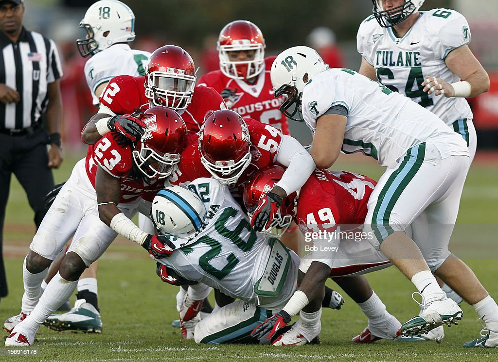Orleans Darkwa #26 of the Tulane Green Wave is tackled by the Houston Cougars defensive line at Robertson Stadium on November 24, 2012 in Houston, Texas. Houston defeats Tulane 40-17.