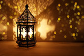 Ornamental Arabic lantern with burning candle glowing at night and glittering golden bokeh lights. Festive greeting card, invitation for Muslim holy month Ramadan Kareem, dark background.