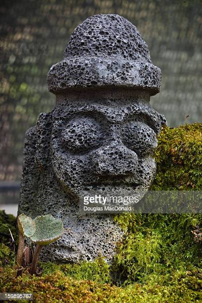 Ornamental stone grandfather covered in moss