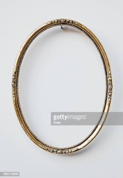 Ornate oval carved gilded picture frame on white wall.