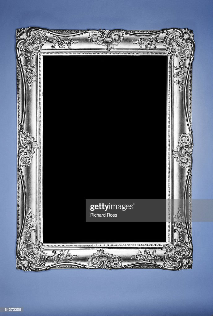 Ornate silver picture frame hanging on a blue wall : Stock Photo