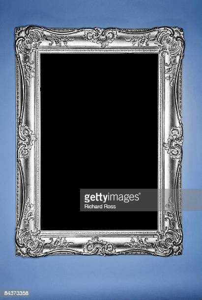 Ornate silver picture frame hanging on a blue wall