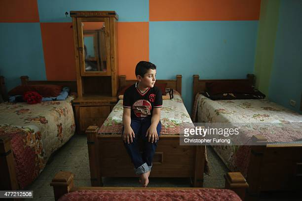 Orphan Abdullah Shimbary aged 8 sits on his bed in the Alamal Institute for Orphans on June 14 2015 in Gaza City Gaza Abdullah was already fatherless...