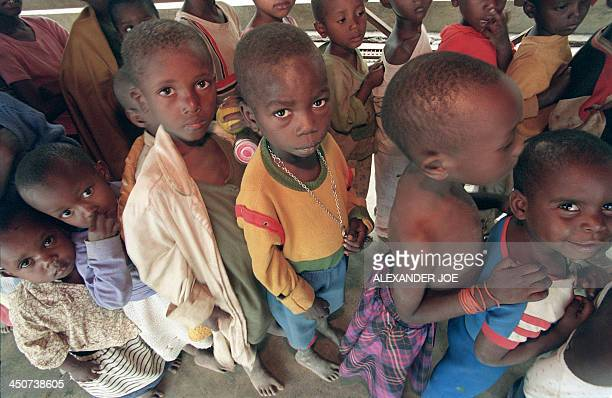 Orphan Rwandan children line up for food on July 17 at the old French school in Kigali The boy in the center is holding a key to he's home that he'll...