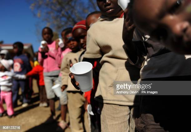 Orphaned and vulnerable children queue for orange juice and hotdogs as they attend a project run by Save The Children at a school in the town of...