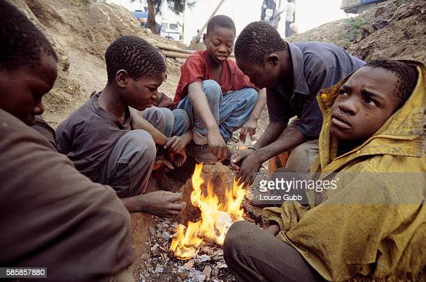 AIDS orphans from the Copperbelt Mining Area who have traveled to Lusaka to try to survive sit around a fire in a drainage ditch Seventy percent of...