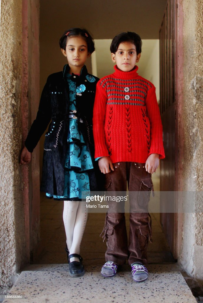 Orphans Randa Monam (L) and Marwa Hassan, who both lost parents in war-related violence, stand in the orphanage where they now live on December 12, 2011 in Baghdad, Iraq. Both of Monam's parents were killed by an explosion in 2005 and Hassan's father was executed in 2008. Estimates suggest there may be more than one million orphans currently in the country, with many having lost parents to war-related violence. Iraq is transitioning nearly nine years after the 2003 U.S. invasion and subsequent occupation. American forces are now in the midst of the final stage of withdrawal from the war-torn country. At least 4,485 U.S. military personnel have died in service in Iraq. According to the Iraq Body Count, more than 100,000 Iraqi civilians have died from war-related violence.