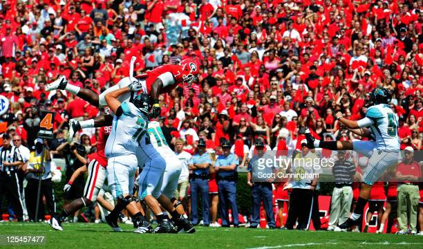 Orson Charles of the Georgia Bulldogs goes up to block a punt against Austin Cain of the Coastal Carolina Chanticleers at Sanford Stadium on...