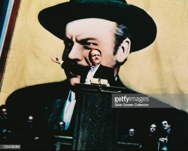 Orson Welles US actor and film director speaking at a lectern with a large portrait of himself in the background in a publicity still issued for the...