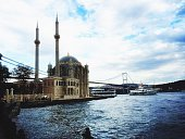Ortakoy Mosque By River Against Cloudy Sky