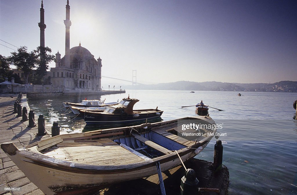 Turkey, Istanbul, Fisherman boats moored in harbour, Ortak?y Cami to the left