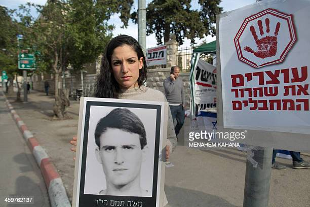 Ortal Tamam a nephew of murdered Israeli soldier Moshe Thamam holds a portrait of him during a sitin protest against the release of Palestinian...