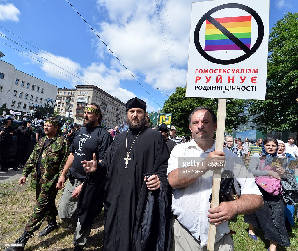 Orthodox believers carry placard reading 'Homosexuality destroys family values' as they march against a Gay Parade in Kiev on May 25, 2013. Around a hundred gay rights activists marched in Ukraine on Saturday despite fears of violence and a court ban, the post-Soviet country's first ever gay pride event.